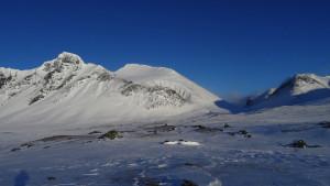 Vzadu náš pokořený vrchol a před ním stany za hradbou sněhu